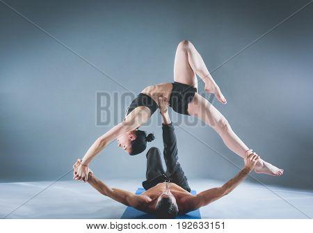 Young couple practicing acro yoga on mat in studio together. Acroyoga. Couple yoga. Partner yoga.