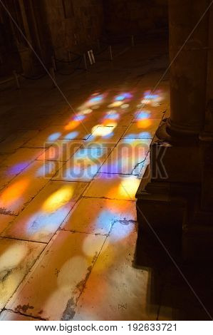 Batalha, Portugal June 04, 2017: Colored flecks of sunlight on the stone floor of the Batalha Santa Maria da Vitoria Dominican abbey Portugal. Batalha Monastery is UNESCO World Heritage Site