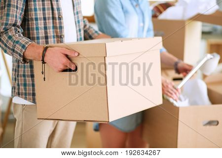 Young couple carrying big cardboard box at new home.Moving house