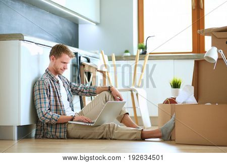 Young man moving in new home.Sitting on floor and relaxing with laptop