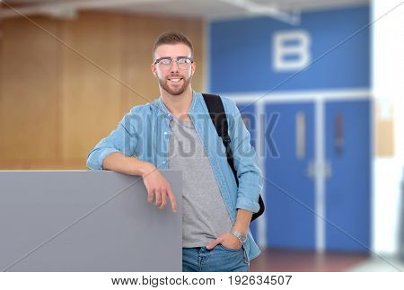 Portrait of a smiling male student holding blank board standing on the street
