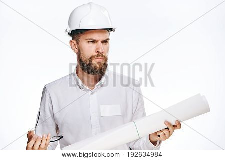 Engineer in a helmet, construction helmet, engineer with a blueprint on a light background.