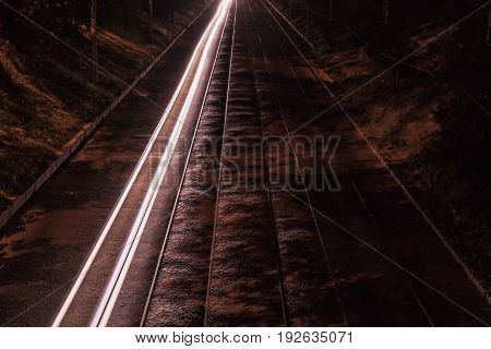 Tram railway next to the track from the headlights of the car. Night scene
