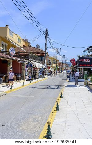 SIDARI, GREECE - MAY 24: View of a typical colorful street in a seaside town full of tourists on a sunny day on May 24, 2017 in Sidari, Corfu island in Greece.