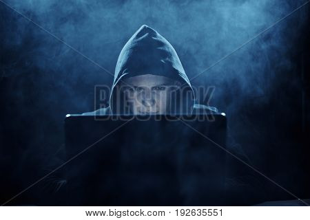 A programmer in a hood, a programmer hacking computer networks, a programmer on a dark background, smoke