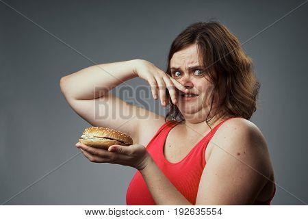 Harmful food, hamburger, hamburger stinks, woman with a hamburger, woman on a gray background.