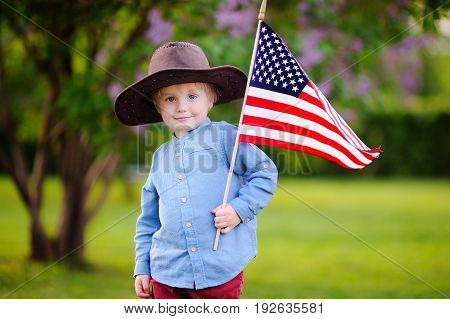 Cute Toddler Boy Holding American Flag In Beautiful Park