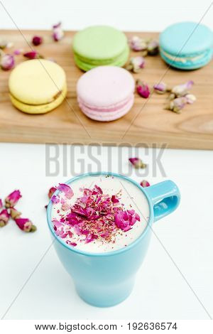 View On Morning French Macarons And A Blue Cappuccino Cup With Rose Petals
