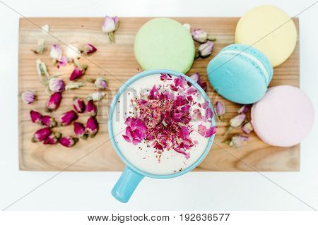 Top View On Morning French Macarons And A Blue Cappuccino Cup With Rose Petals