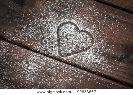 shape of a heart with powdered sugar on wooden background