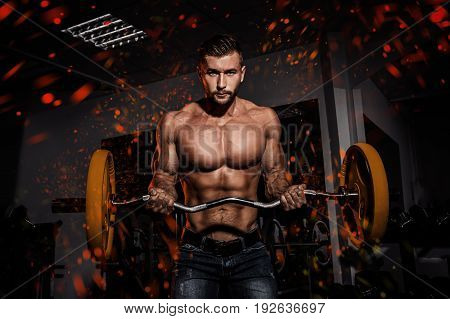 Fire and flame design. man in gym. Muscular bodybuilder guy doing exercises with barbell. Strong person. Sports background. Young athlete ready for weight lifting training.