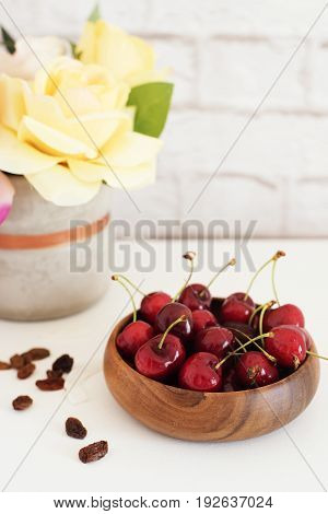 Fresh Cherries In A Wooden Bamboo Bowl. Bright Brick Wall Background. Yellow Roses In A Vase. Health