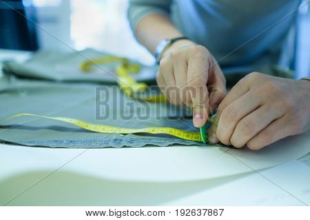 Closeup of skilled caucasian tailor working. Hands marking and measuring fabric while making clothes