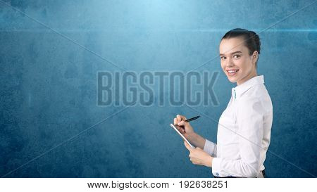 Professional Confident Businesswoman With Bun Writing In Her Organizer Isolated On Studio Background