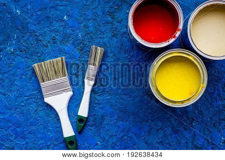 Colorful paints and brushes on blue wooden desk background top view.