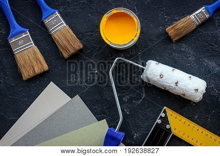 Set of tools for painting on black stone desk background top view.