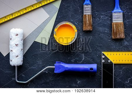 Set of tools for painting on black stone table background top view.