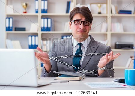 Businessman tied with chains to his work