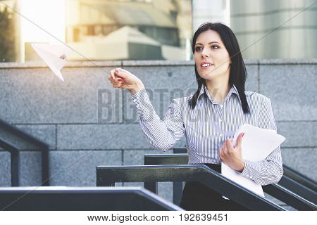 Fly Away. Portrait Of Attractive And Cheerful Business Woman In Smart Casual Wear Launching Paper Pl