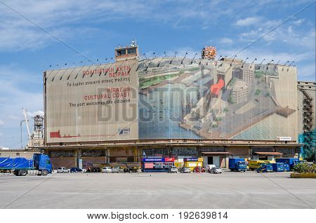 Port of Piraeus Greece - Mai 30 2017: Wall painting on one of the old silo and dry docks buildings in the industrial area of Silos Ietioneias Coast with its Floating Museum