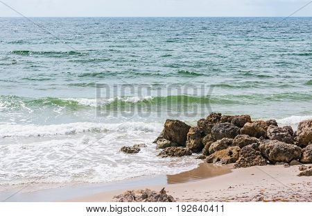 waves crashing on beach shore rocks on a hot summer day in South Florida