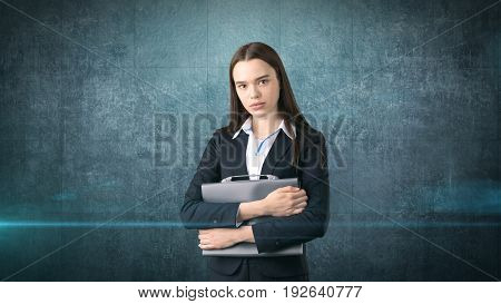 Young Serious Beautiful Businesswoman Portrait With Gray Briefcase, Dark Background
