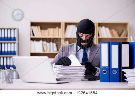 Criminal businessman with balaclava in office