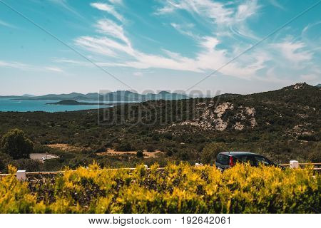 Parked car behind hedge in summer mountain landscape.