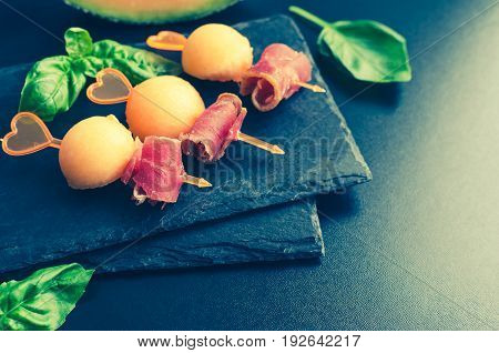 Colorful canape on skewers with melon and prosciutto on a slate plate on dark background. Tasty appetizer for a party or banquet. Concept of italian food. Traditional appetizer antipasto. Copy space.