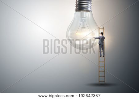 Businessman on ladder with light bulb