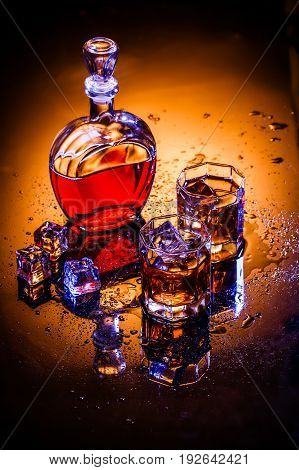 Decanter and two glasses with whisky and ice on gray background, photo in studio