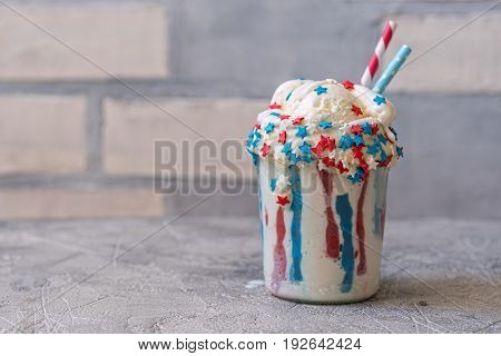 Vanilla funfetti milkshake with whipped cream and sprinkles. Patriotic drink cocktail