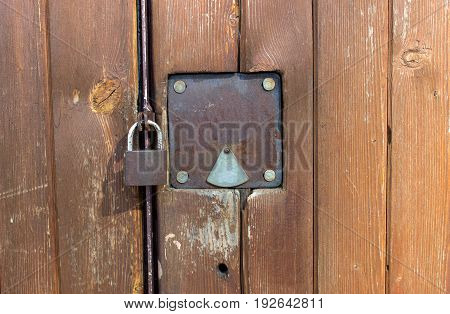 The lock hangs on the wooden door near the keyhole