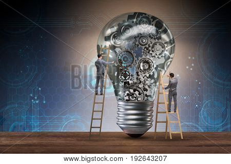 Businessman on ladder repairing light bulb