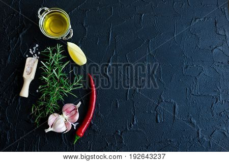 Rosemary garlic lemon chili pepper and olive oil on dark stone table. Herbs and spices concept. Cooking ingredients. Food flat lay. Creative layout with place for text. Copy space. Top view.