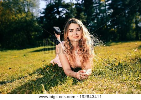 Happy girl lying on the grass and smyling. Attractive girl dreaming in summer time