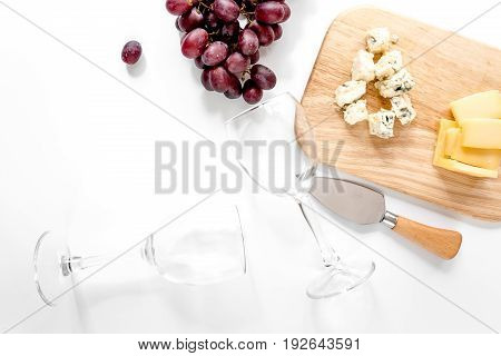 Bottle of red wine and wine glasses with cheese and grape aperitive on white background copyspace.