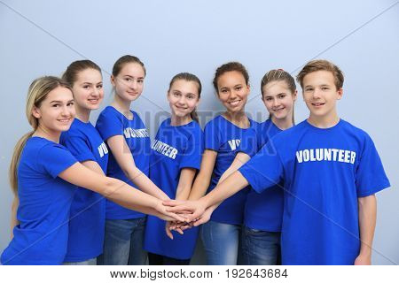 Team of volunteers putting their hands together as symbol of unity, on color background