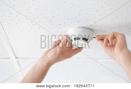 Electrician installing smoke detector on ceiling, closeup