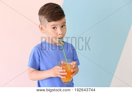 Cute little boy drinking juice on color background