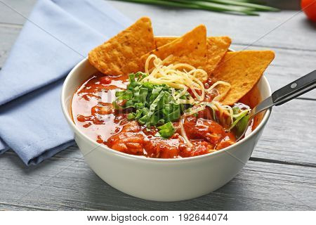 Bowl with delicious chili turkey and nachos on wooden table