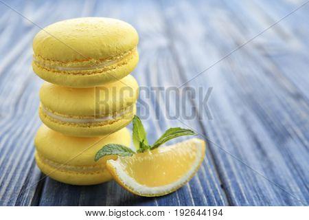 Tasty lemon macarons on wooden table, closeup