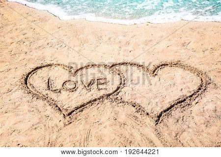 Word LOVE and hearts drawn on sand near water. Romantic concept