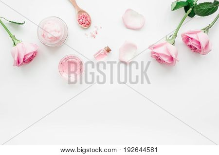 homemade spa with rose cosmetic set, cream, salt and oil on white desk background top view mock-up