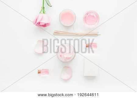 cosmetic set with rose blossom and body cream for treatment on white desk background top view