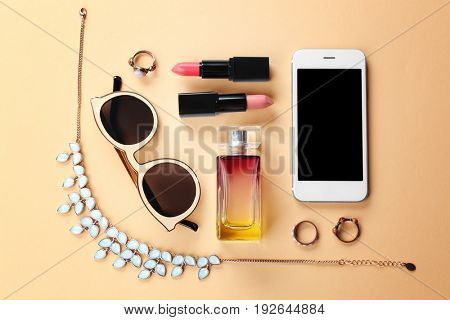 Perfume, accessories, cosmetics and phone on light background