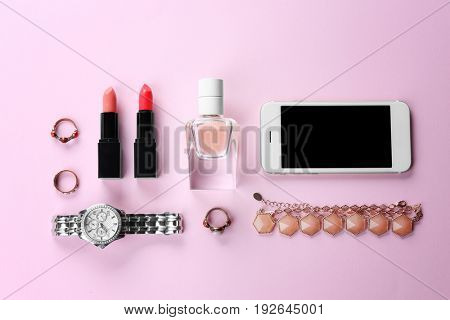 Perfume, accessories, cosmetics and phone on pink background