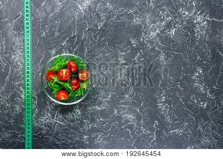 Slimming diet. Salad and measuring tape on grey table background top view copyspace.