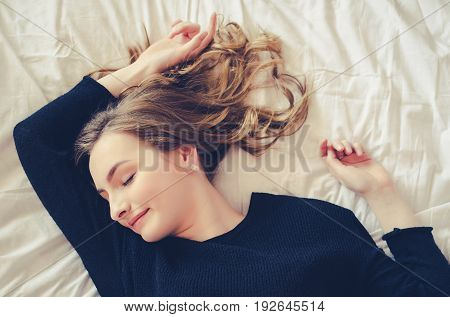 Beautiful teen girl wearing black top and sleeping in the bedroom. Portrait of a young woman naps daytime sleep on the bed at home with positive emotions facial expression. poster