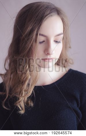Beautiful female teenage model wearing casual black top looking down with shy and thoughtful expression on her face. Headshot of student girl with curly fair hair and clean healthy skin.